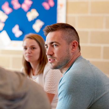 Side view of man in deep discussion with group in community centre setting     Download